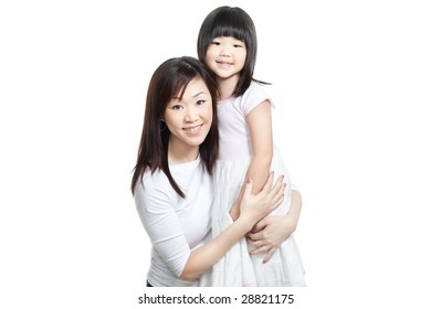 Chinese young mother and daughter both with long hair hugging one another for a family portrait