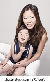 Chinese young mother with eurasian daughter sharing a mother of joy and fun in a family portrait