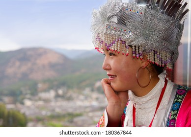 Chinese young woman in ethnic dress and hat