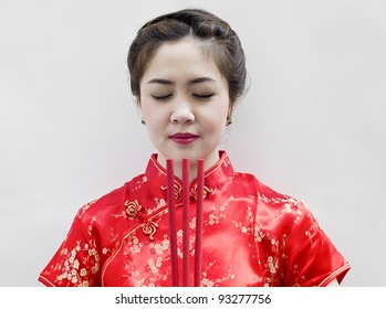 chinese young woman with tradition clothing holding joss sticks(incense)