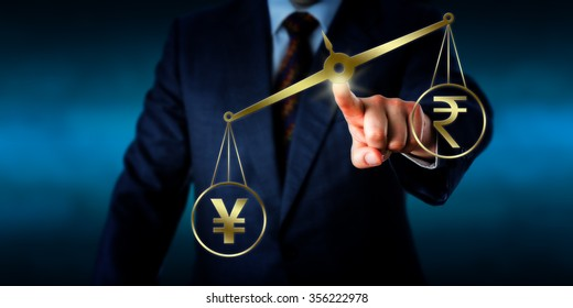 Chinese yuan symbol or Japanese yen sign is outweighing the Indian rupee sign on a golden pair of scales. Business concept for the modern foreign exchange market and global finance.