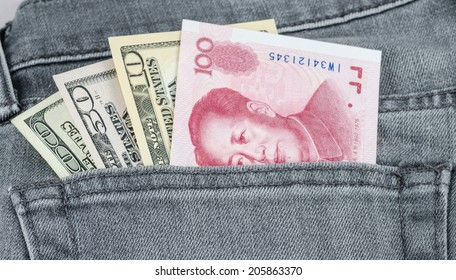 chinese yuan and US dollar banknote in the grey jean pocket