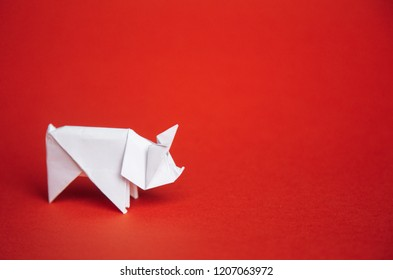 Chinese Zodiac Sign Year of Pig. green origami paper tree and white pig symbol of 2019, on a red background, free space for text, minimalism. Happy New Year 2019 year