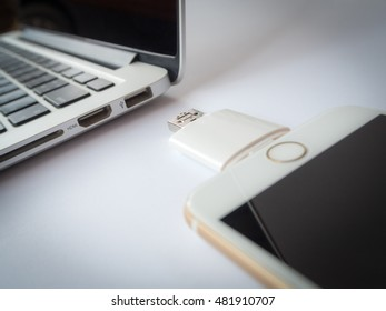 CHINGRAI, THAILAND -SEPTEMBER 7, 2016: Close-up image of two way external flash storage transfering data with Apple iPhone 6 and close to Apple Macbook Pro Retina. Focus with USB connector.