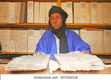 Chinguetti, Adrar Province / Mauritania -Photo taken September 2009 : Man in a library of the desert showing very old books, Chinguetti