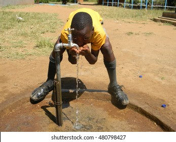 Chinhoyii,Zimbabwe,March 23 2015. A  school  boy  drinks  water directly  from  a  tap using his  hands.Most  places  in  rural  Africa  do  not  have  running  water.