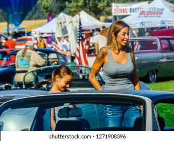 Chino Hills, California / USA - June 3, 2017: A mother and daughter stand smiling next to many vintage Porsche automobiles at the Friends Of Steve McQueen Car and Motorcycle Show