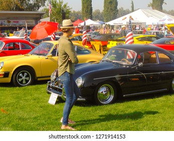 Chino Hills, California / USA - June 3, 2017: A tall beautiful woman wearing a hat, jeans and long sleeve blouse admires a 1958 356A Super Porsche automobile at the Friends Of Steve McQueen Car Show