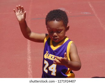 Chino Hills, California / USA - June 3, 2017: A young African American boy wearing a Los Angeles Lakers jersey of Kobe Bryant is walking at the Friends Of Steve McQueen Car and Motorcycle Show