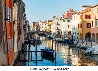 Chioggia, Venice, Italy: city landscape with canal, ancient bridge, boats and colorful reflections on the water in the picturesque old town