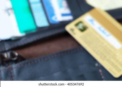 chip at back side of gold credit card shown signature on black wallet with other cards in blur mode