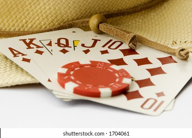 A chip is placed on a royal flush with a hat in the background.  The bottom of the image is white to easily integrate into a design of your choice.