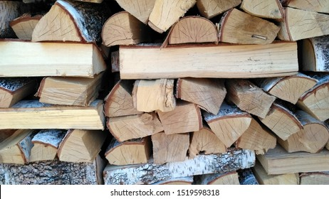 Chipped firewood is on the heap. Woodpile of firewood close-up. A stack of dry firewood, visible texture and cracks in the tree. Exterior shot of a large pile of firewood in soft daylight