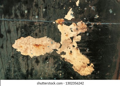 Chipped paint, drippings, scrapes and stains on hull of tired fishing boat