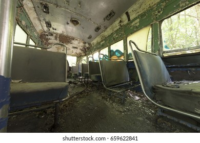 Chipped and peeling seats covered in debris inside abandoned trolley car.