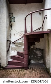 Chipped plaster walls and an old spiral staircase in historic Smithville Village in New Jersey.