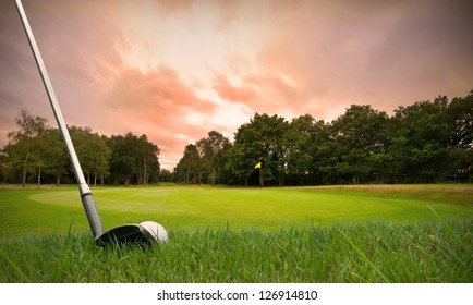 chipping a golf ball onto the green with golf club at sunset with copy space