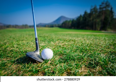 chipping a golf ball onto the green with driver golf club. Green grass with forrest and mountains in the background. Soft focus or shallow depth of field. Side view