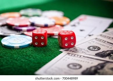 Chips of colored casinos placed on the green table are coins that are used to bet in casinos. Concept about entertainment and gambling