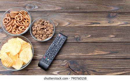 chips, crackers, a remote from the TV on a wooden background. watching films.