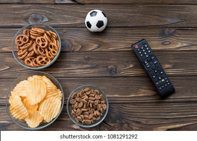 chips, crackers, snacks, snacks for beer, soccer ball, remote from the TV on a wooden background. football fans.