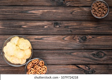 chips, crackers, snacks on the background of a wooden table. beer snacks.