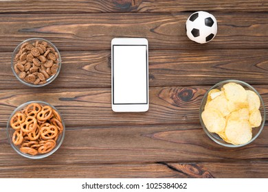 chips, crackers, snacks, a smartphone, a soccer ball on a wooden background. fans. Soccer game.