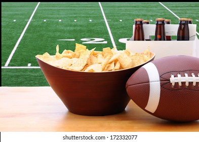 Chips, football and Six Pack of Beer on a table in front of a big screen TV with a Football field. Great for Super Bowl themed projects. Horizontal format.