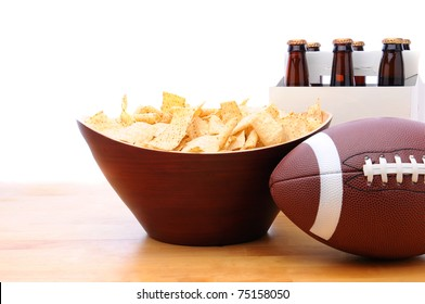 Chips, football and Six Pack of Beer on a table with a white background. Horizontal format. Great for Bowl Game projects.
