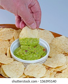 Chips & Guacamole against in a wooden serving platter against pale background