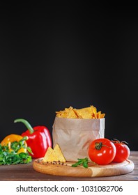 Chips Nachos in the package. Peppers and tomatoes. The concept of food and delicious snacks.