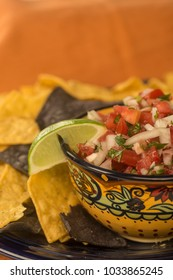 Chips and Pico De Gallo in an ethnic bowl with lime against and orange background