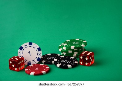 chips and poker dice on green background