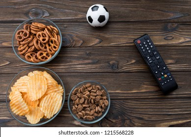 chips, snacks, crackers, snack for beer, soccer ball, TV remote on the background of a wooden table. fans, football game.