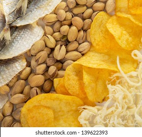 Chips, squids, pistachios and salty fish to beer. Background