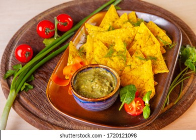 chips with tomato and avocado sauce on a plate in the studio