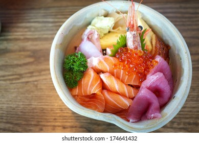 Chirashi sushi bowl with salmon, tuna, shrimp, salmon roe, eel, sea bass, sweet omelette and imitation crab meat served with wasabi
