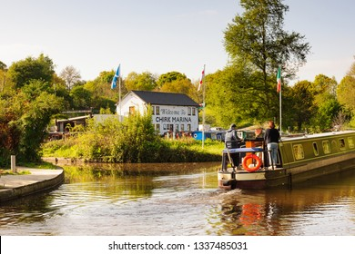 Chirk Wales UK - May 8 2017: Barge with holiday makers passing the Marina with narrowboats moored up in front of the boat hire and maintenance centre on the Llangollen canal in North Wales
