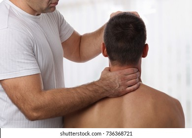 Chiropractic back adjustment. Muscular Man suffering from back and neck pain.