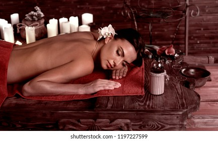 Chiropractic massage therapy of woman in spa salon. Girl on candles background in massage spa salon. Luxary interior in oriental therapy salon. Brown sepia on dark .
