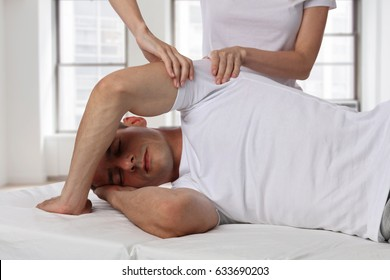 Chiropractic, osteopathy, manual therapy, acupressure. Therapist doing healing treatment on man's back. Alternative medicine, pain relief concept. Rehabilitation after Back Injury, Physical therapy.