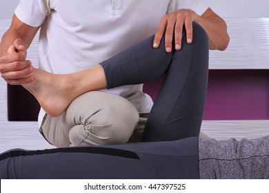 Chiropractic, osteopathy, manual therapy. Therapist doing healing treatment on female leg / knee . Alternative medicine, pain relief concept