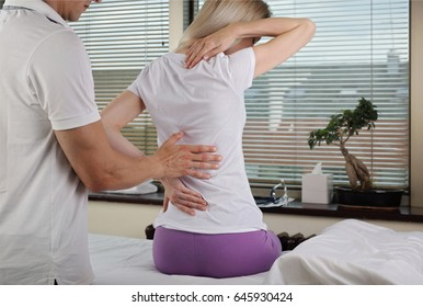 Chiropractic, osteopathy, Physiotherapy, Sport injury Rehabilitation. Alternative medicine, pain relief concept. Woman patient suffering from back pain during medical exam.