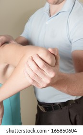 Chiropractor adjusting young female patient elbow with his hand