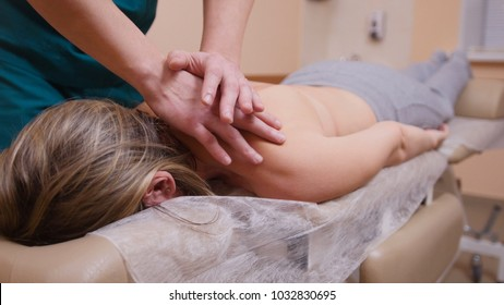 Chiropractor massaging a woman lying on a massage table