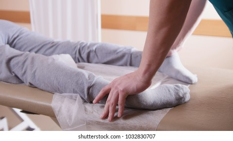 Chiropractor massaging a woman lying on a massage table, stretching her feet, close-up of legs