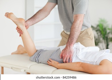 A chiropractor stretches a female customer's leg in his surgery