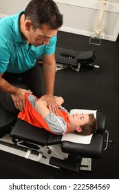 A Chiropractor treating a young boy