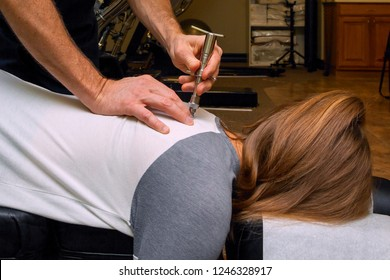 Chiropractor uses an Integrator on the back of a young girl to align her spine and reduce subluxation.  She is laying face down on a chiropractic table.