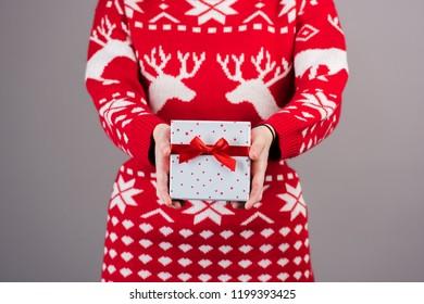 Chirstmas gift being held by a female wearing a chirstmas jumoer